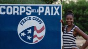 Black woman Peace Corps Volunteer smiles next to Peace Corps sign in French.