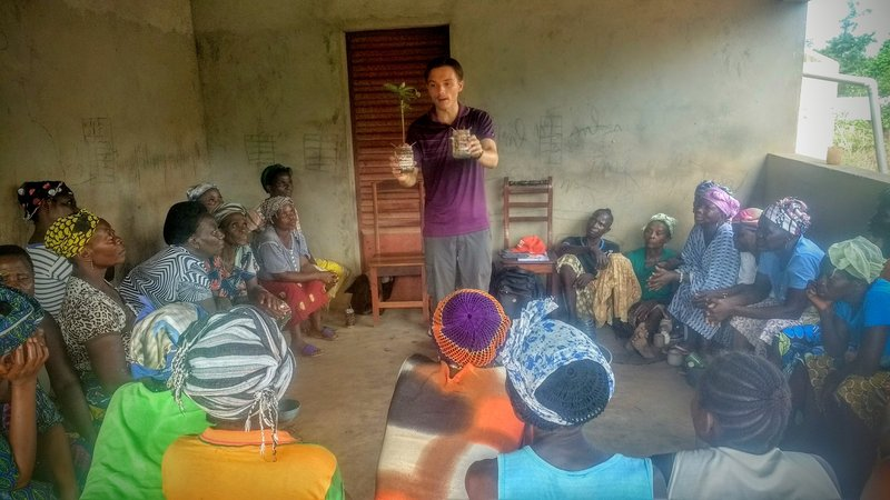 A young male Volunteer holds a sapling in the middle of a classroom while teaching