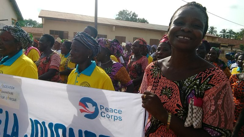 a Beninese woman smiles while marching in a parade with a Peace Corps banner