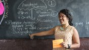 A Puerto Rican woman stands teaching at a blackboard, smiling.