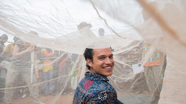 A Volunteer sits under a bed net