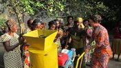 """Help Mamas Earn: Help Mamas Earn: Me """"passing"""" the red oil machine off to the women's group"""