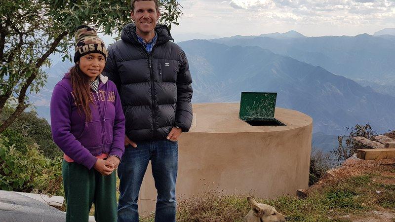 Voluntario retornado Adam Carroll y socia comunitaria, con cisterna co-instalada de captación de agua pluvial, 2019