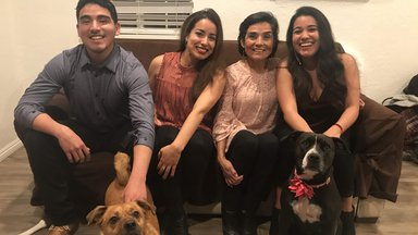 Fiorella's brother, sister, mom, and two dogs sit together on a couch