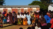 Malawian women with colorful skirts gather to welcome new Trainees outside of a school house