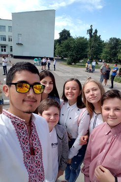 A young Mexican American man wearing traditional Ukrainian clothes stands smiling with his young, Ukrainian students outside.