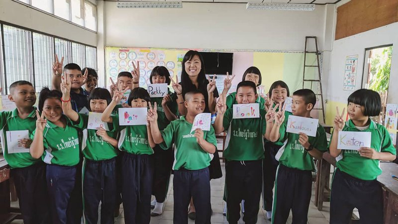 Volunteer Andrea poses with a class of primary school kids. They all hold up homemade name tags and peace signs.