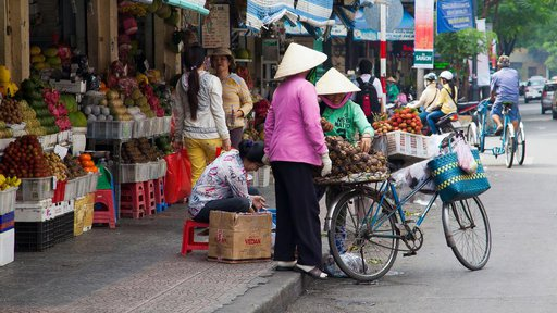 Shoppers load fruit onto a bicycle at an open-air market.