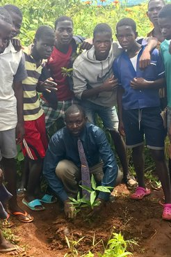 A group of Malawian students and their teacher stand around a newly planted bamboo seedling