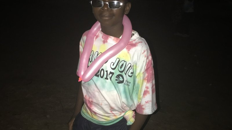 A Child with his camp t-shirt, smiling with a balloon animal around his neck.