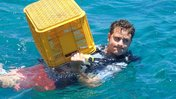Carrying a crate for coral at coral gardening training