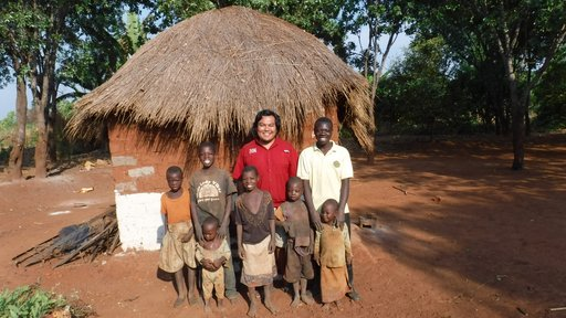 A Volunteer of Native American heritage stands in front of a Zambian home with a large family, smiling.