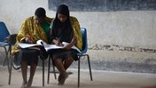 Two Malawian sit together and write in notebooks in a classroom.