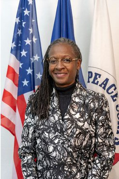 A Black woman smiles in front of an American flag and a Peace Corps flag.