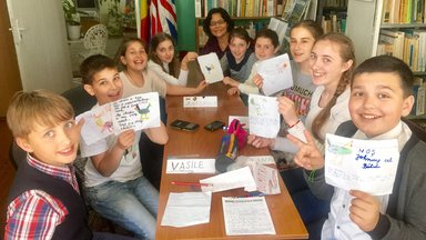Older American woman with her Moldovan class as they show their projects.