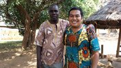 A young man of Native American heritage stands outside next to an older man of Zambian heritage.
