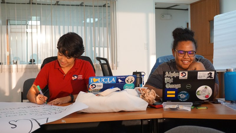 Diane smiles as she works on her computer. To the left a coworker works on a poster.