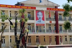 Portrait of Ho Chi Minh and banner hangs from the eaves of a Hanoi school.