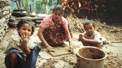 A Nepali mother and her children in the courtyard of their home.
