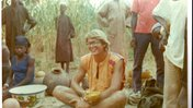 A male Volunteer in the mid-70s shares a meal in his Burkina Faso community.