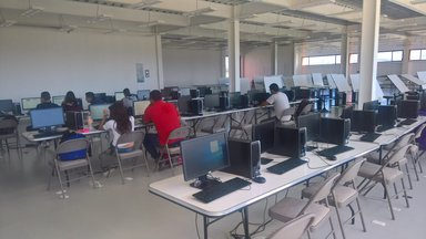 Several rows of desks with computers.