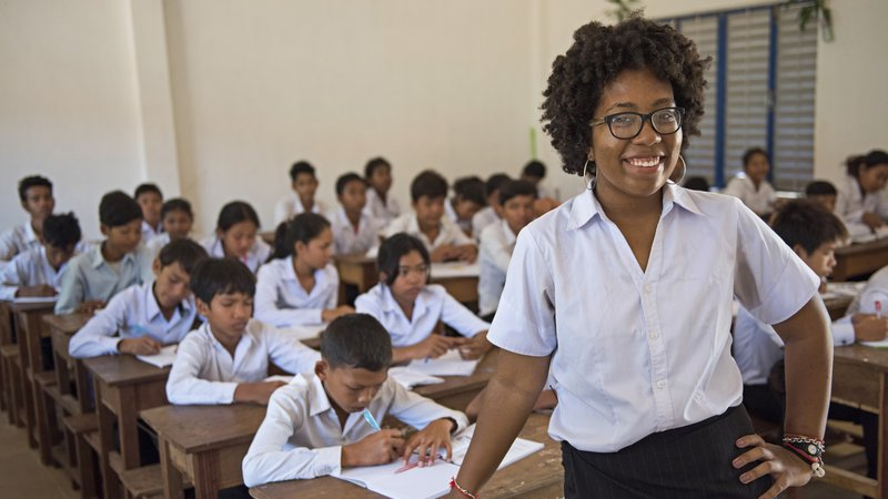 A Black woman leans on a school desk, smiling in front of her students, who are working on an assignment in the background