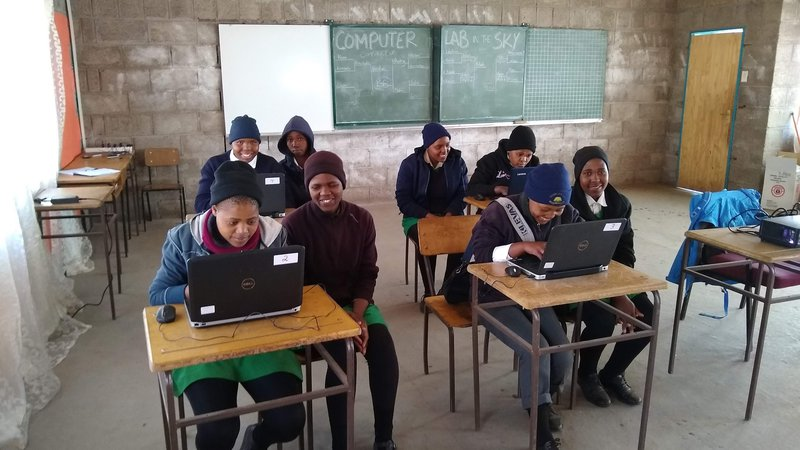 Young African adults (Grade 11) in Western-style clothing work on computers in a classroom in Lesotho.