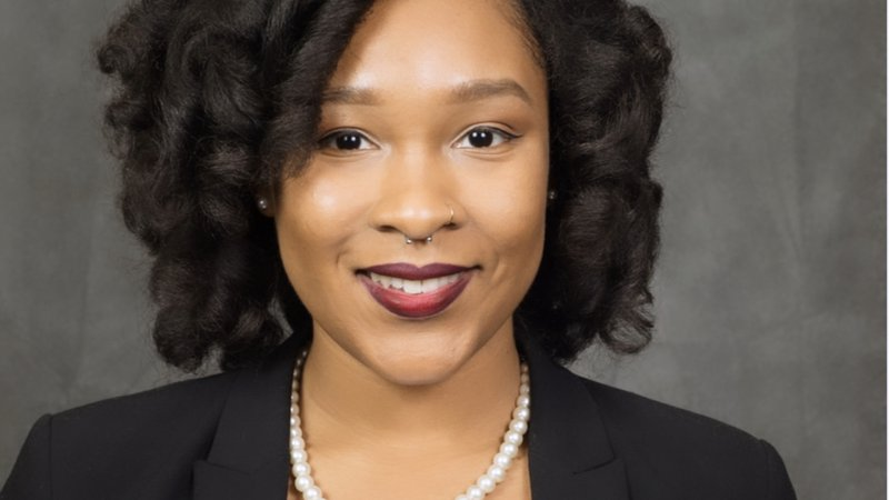 A young Black woman smiles in a professional headshot
