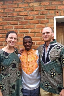 Two Volunteers and their counterpart smile together for a photo