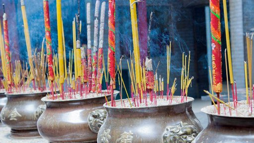 Pink, yellow, and red incense sticks stand upright in four urns at a temple.