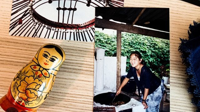 A picture of a picture of an Asian American Volunteer bending over a basket outside to work..