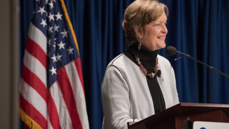 Jody Olsen stands at a podium that displays the Peace Corps logo