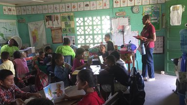 Several kids sitting down in a classroom