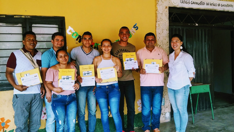 A group of people in Colombia stand outside smiling in front of a yellow wall.