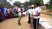 Four adult people stand infront of a crowd of Tanzanian school children holding malaria net materials.