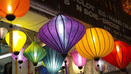 Hanging lanterns of different colors and shapes light up the entrance of shop.