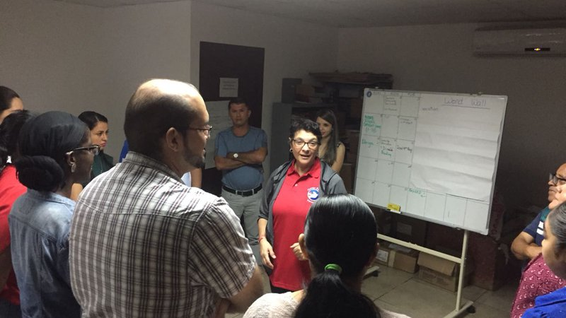 An American woman wearing a red Peace Corps polo gives a presentation in front of a group of her peers inside of an office.