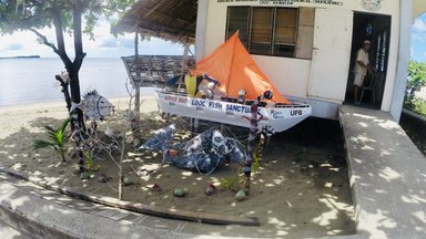 A little boat in front of a building on the beach- the Looc Fish Sanctuary