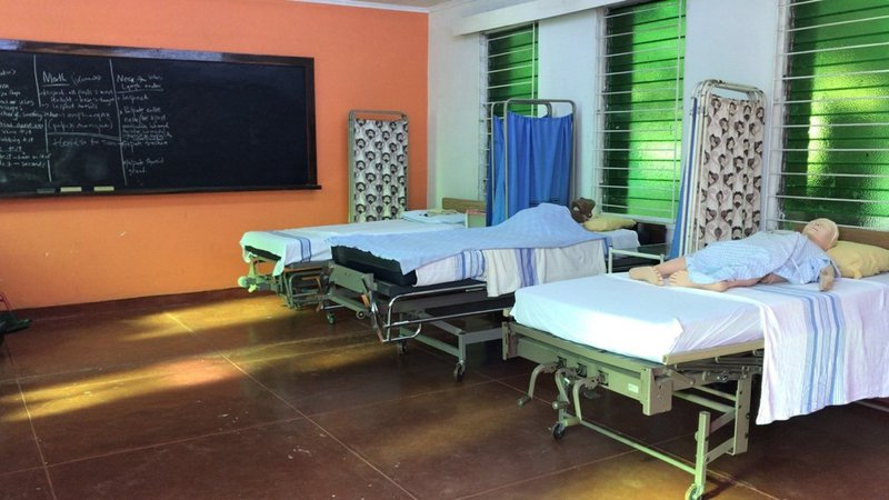 Three hospital beds lined up next to each other with mannequins on each bed