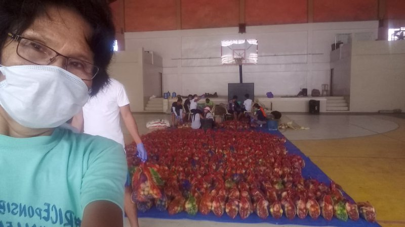 A woman wearing a mask stands in front of hundreds of bags of recently packed produce