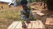 Madame Victorine Chia displays the beehive that she built after a technical session on hive construction
