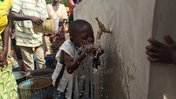 Community members and children gather to collect water from the solar powered filtration system.