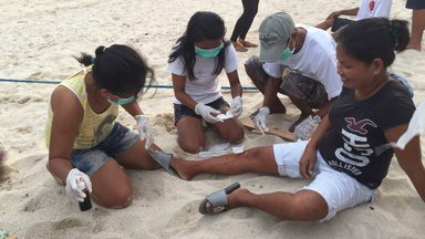 3 people with masks practicing First AID on invididual