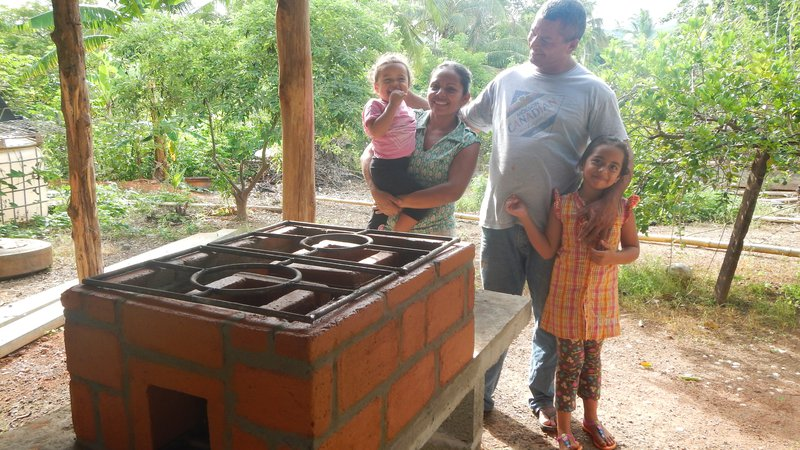 a Panamanian family smiles in front of an eco-stove