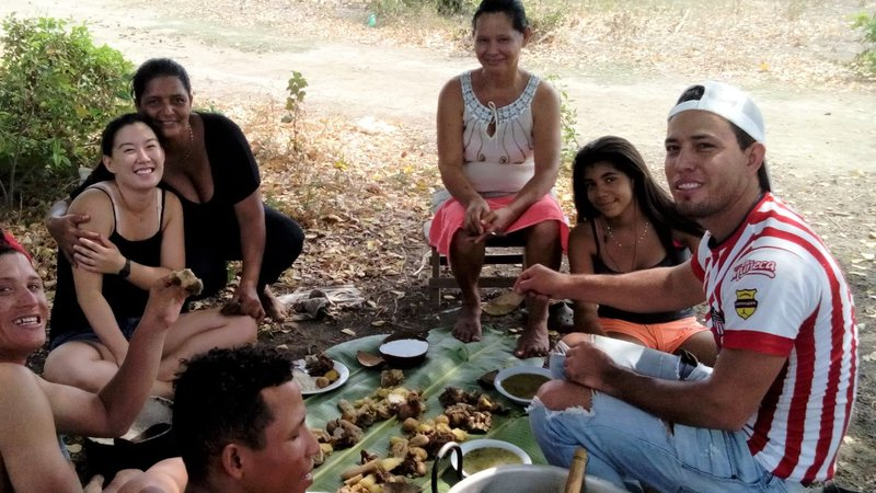 A group of people eat a picnic outside