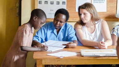 PCV Caroline and her counterpart sit at a desk as a child writes the family's name on the log in sheet.