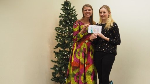 Peace Corps Volunteer Rachel Wallace with an Edison student and one of the books created for students in Senegal.