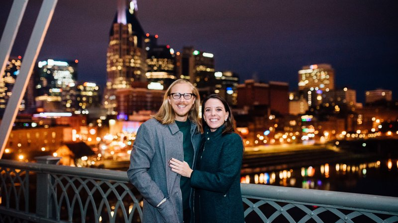 Two people stand in front of a nighttime city skyline.
