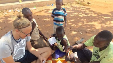 A Peace Corps Volunteer plays with children in Uganda.