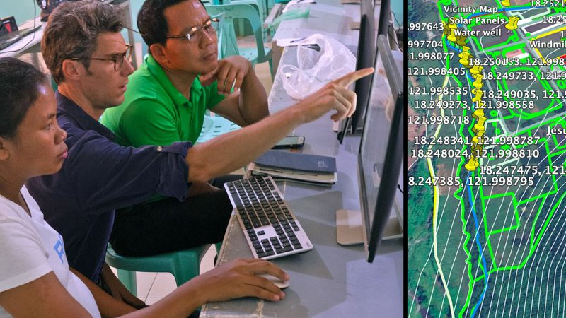 A American male sits with Filipino colleagues looking at a data map on a computer